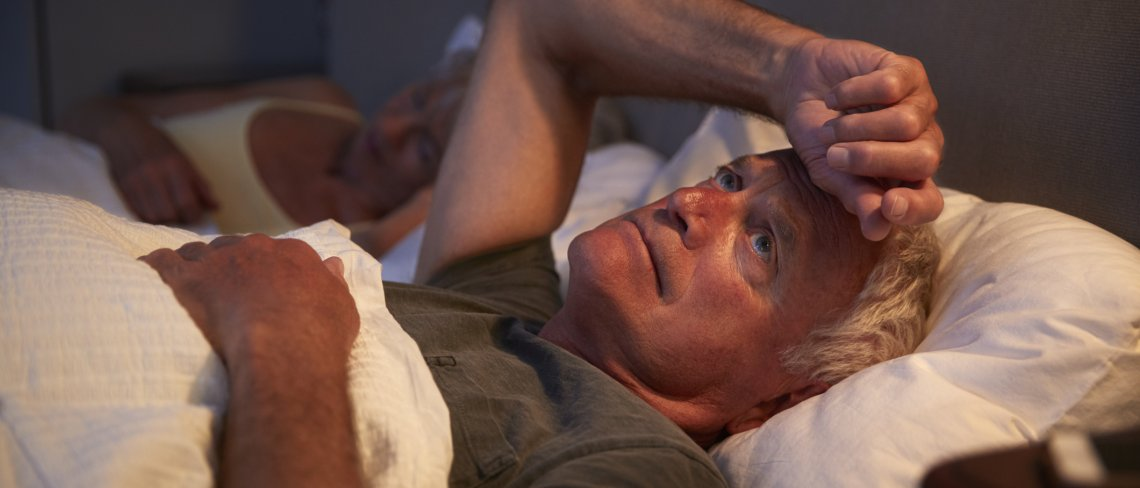 Man in bed suffering with insomnia with his hand on his head