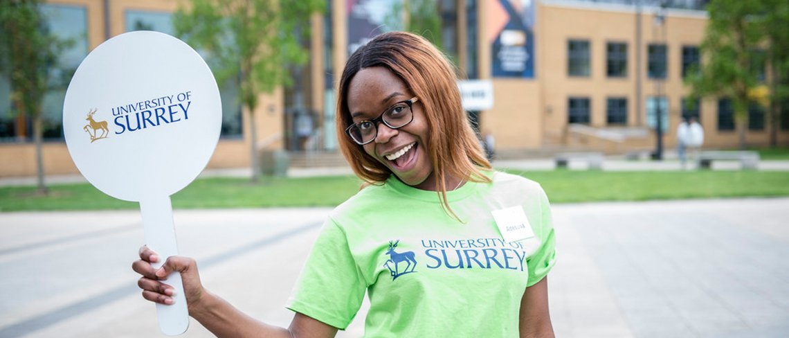 Student holding up University of Surrey sign