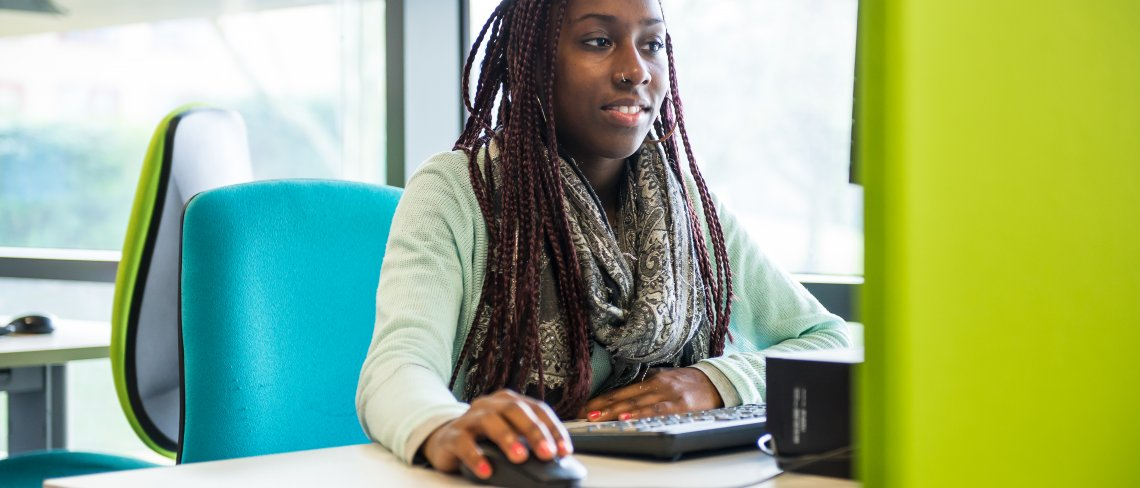 Female student using the computer at the library