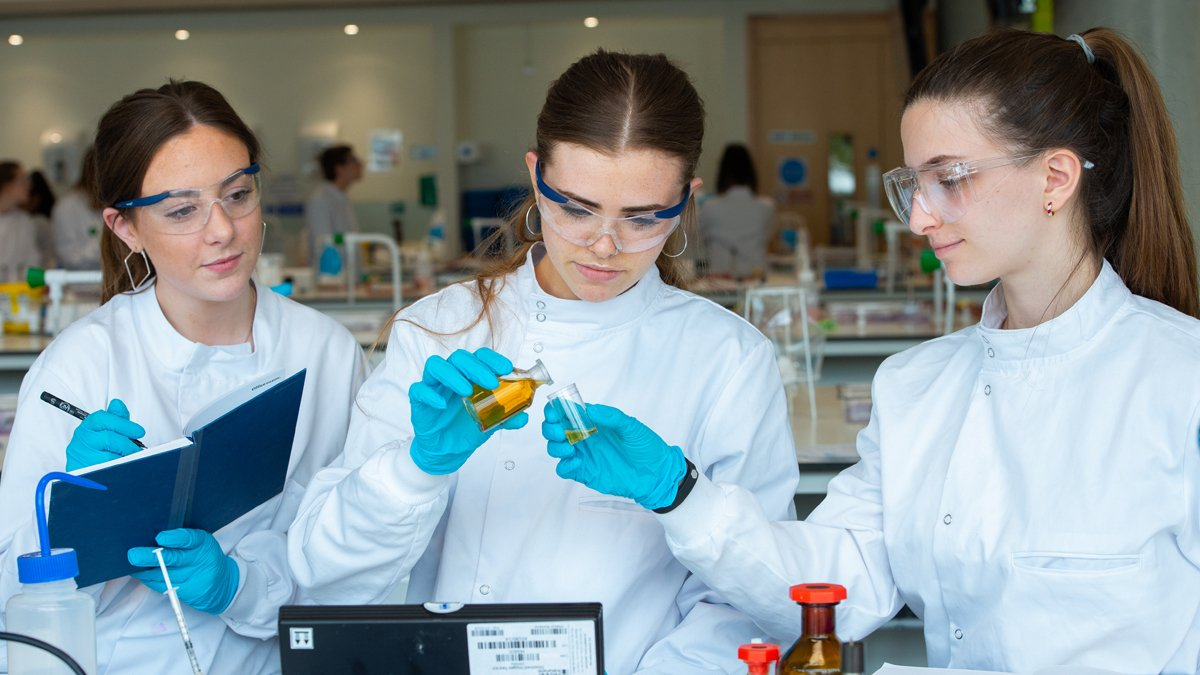 Three students holding vials and writing during a practical session in a lab