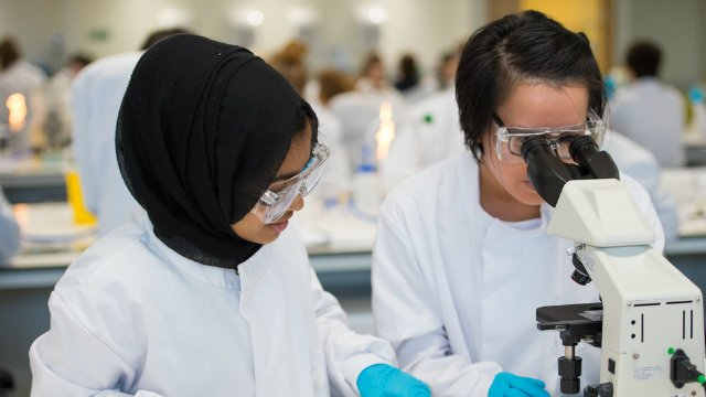 Two biosciences students looking through a microscope