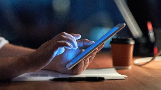 A person using a tablet at night