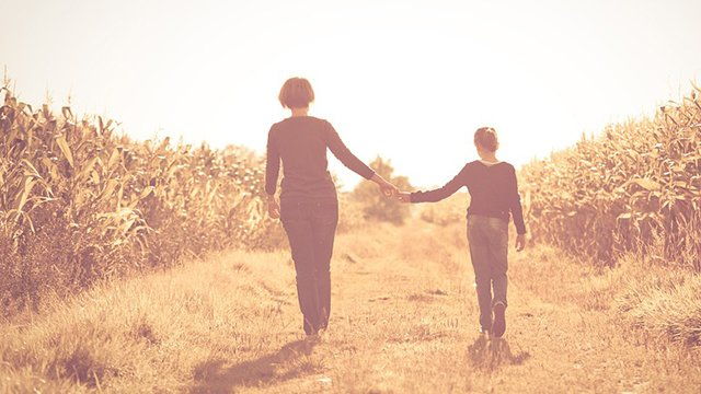 A mother and daughter walking hand in hand through a golden field
