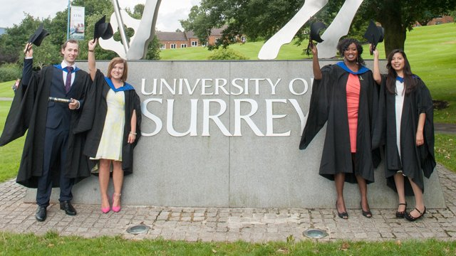 Graduates standing in front of the stag on campus