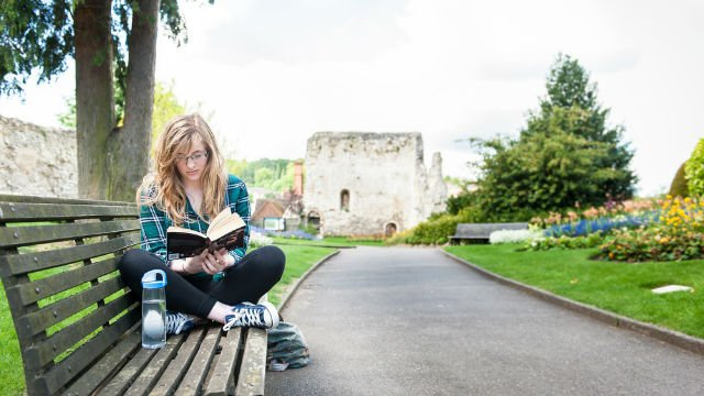 A student reading by Guildford castle