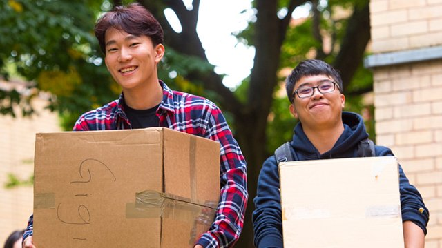 Two male students moving in carrying boxes