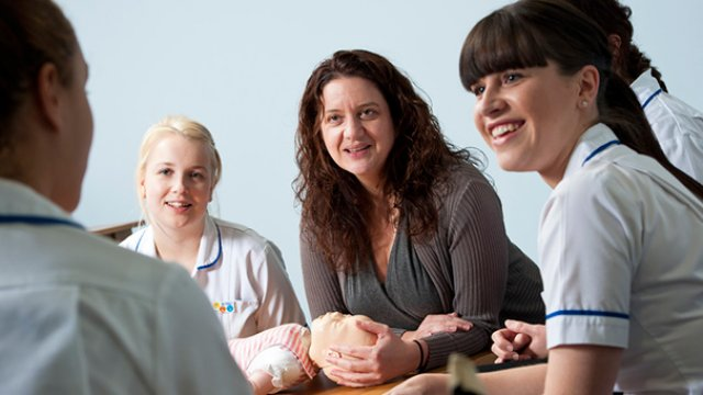 Midwifery students with a sim baby