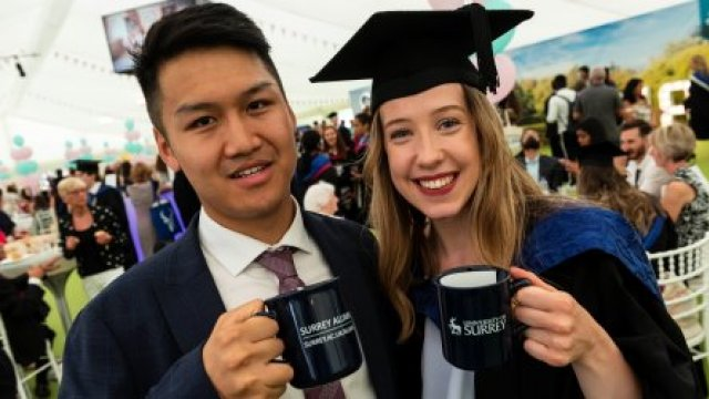 Male and female graduate holding Surrey mugs