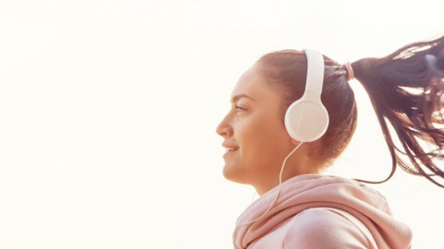 Woman running listening to music through headphones