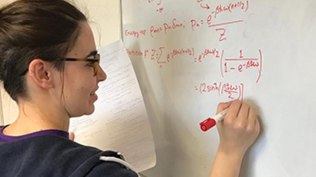 A student writing an equation on a white board