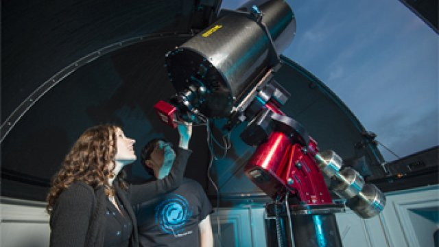 Woman using a large telescope