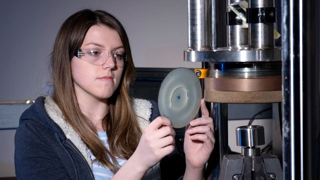 Female student using mechanical engineering equipment