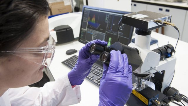 Female using a microscope