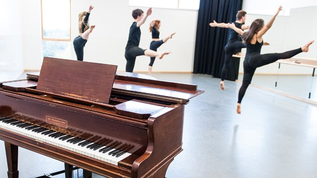 Student dancing with piano in foreground