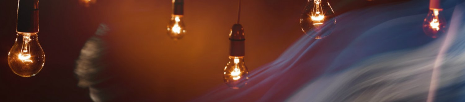 Lightbulbs in darkness with a blurred moving figure