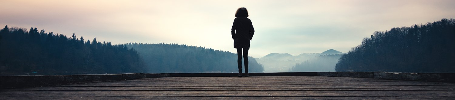A women standing on the end of a jetty looking at a mountain range