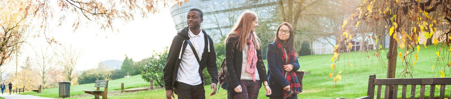 Three students walking in through the park with the Duke of Kent building in the background