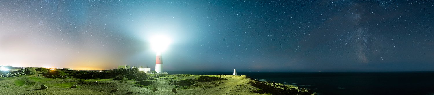 A lighthouse shining it's light into the starry night skly