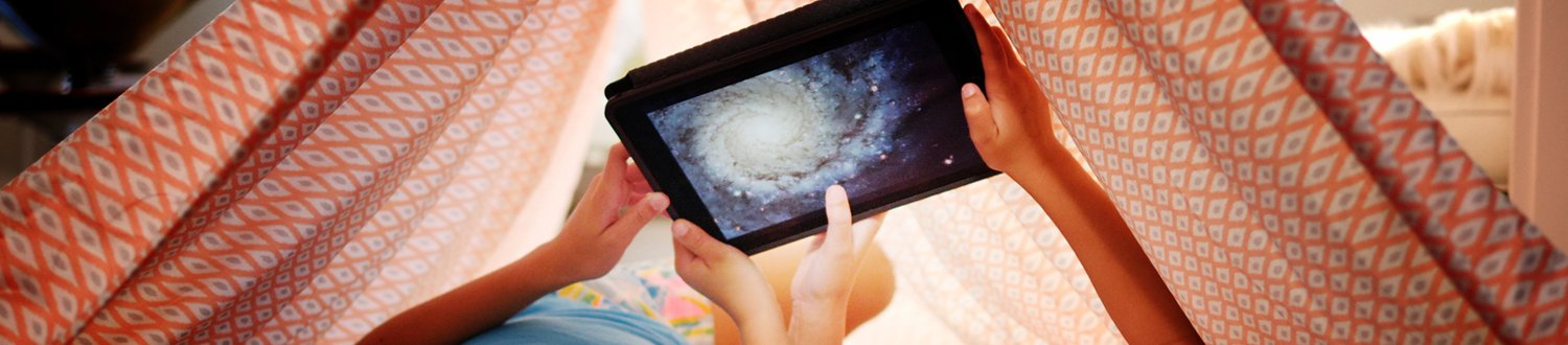 Children holding up tablet with solar system on it