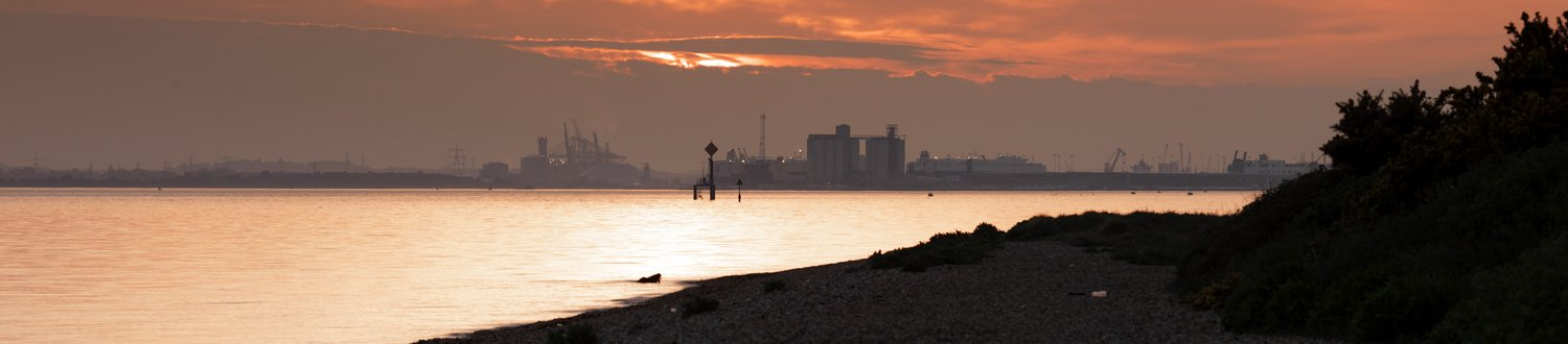 Chemical factory across the water at sunset