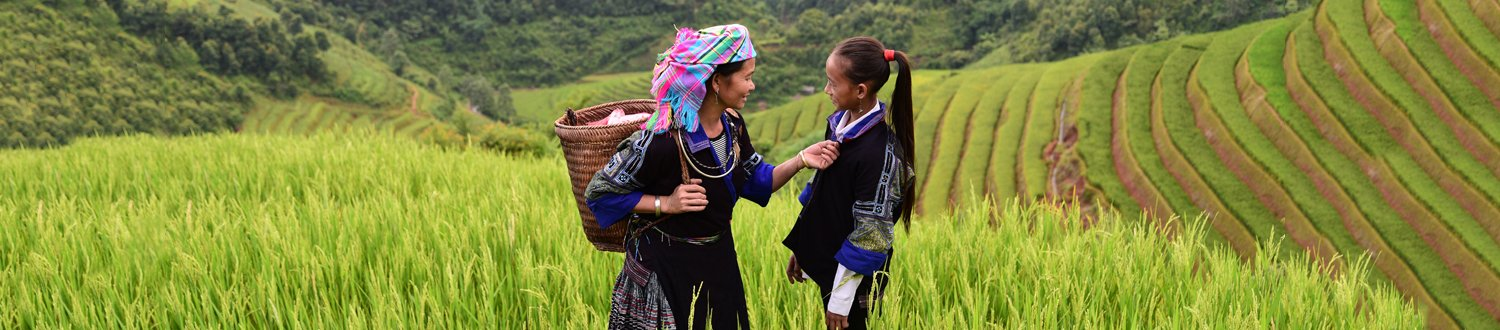 Two women talking with green fields surrounding them