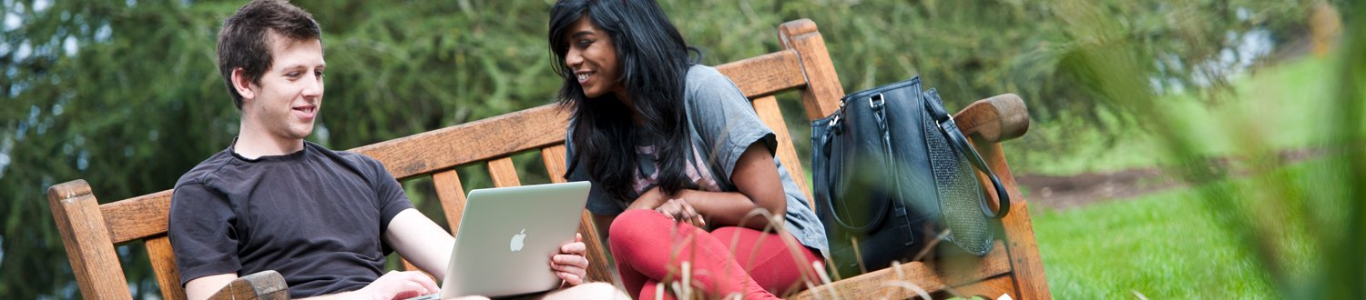 Students sat looking at a laptop on a bench