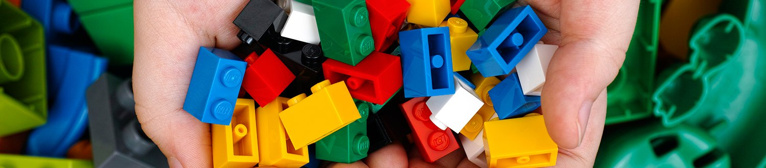 A pair of cupped hands holding lots of different coloured Lego bricks