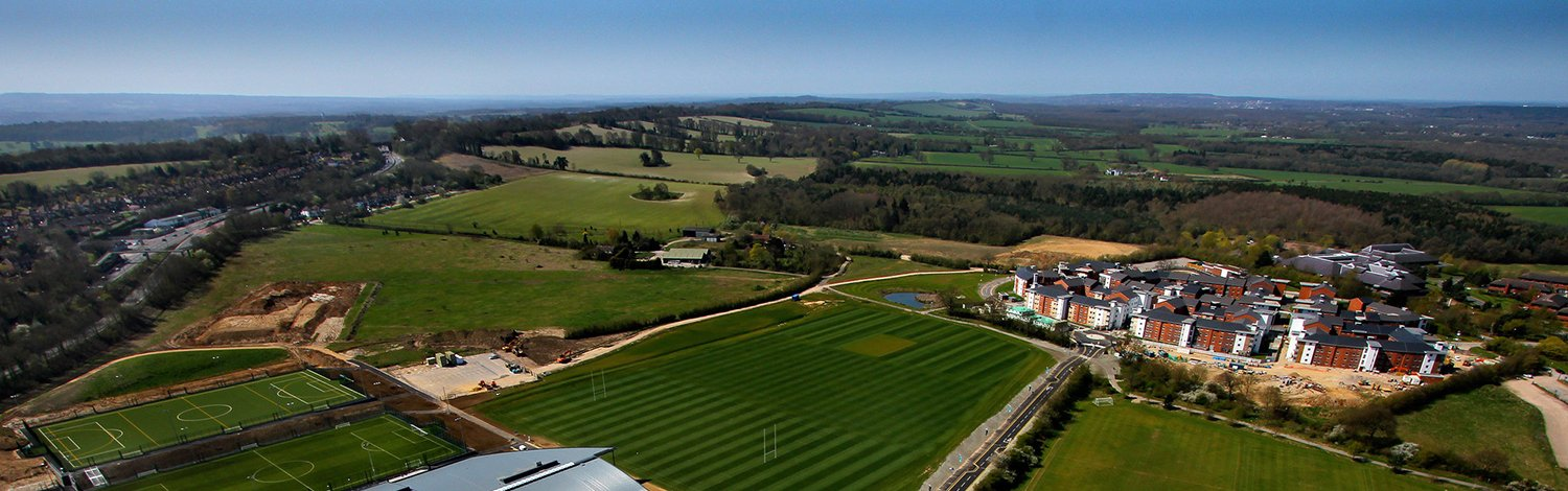 Ariel shot of Surrey Sports Park, showing blue sky and green grass