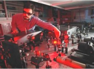 Man with safety glasses tweaking a laser beam in a laboratory