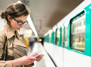 Commuter lady waiting for a train using her smartphone