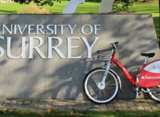 Red Santander bike in front of the University of Surrey stag statue