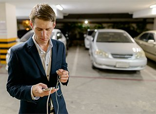 A man is looking at his phone in front of a silver car