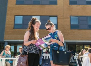 Two girls reading the open day brochure outside the Surrey Business School