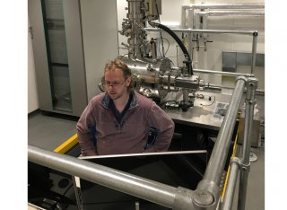 David Cox, a focussed ion beam expert from the University of Surrey and the National Physical Laboratory performing commissioning tests at the console of the new SIMPLE tool in its new laboratory at Surrey.