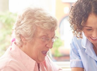 Nurse laughing with elderly woman