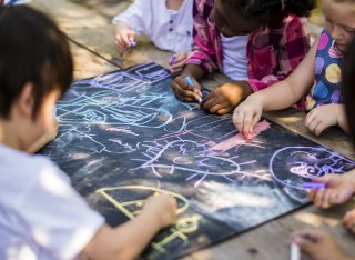 Children in a nursery drawing on the ground