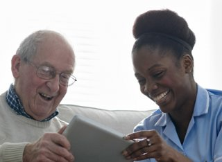 Elderly man using a tablet alongside nurse