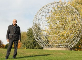Jim Al Khalili stood next to Surrey University globe sculpture
