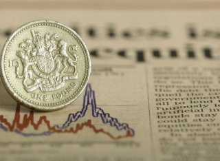 A pound coin sits on a financial newspaper