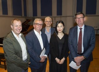 Competition winner Zixuan Yu is joined by the panel of judges