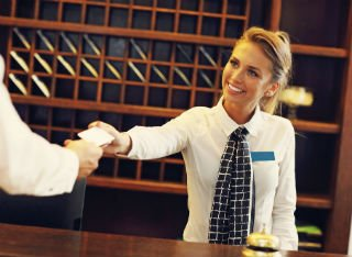 A lady serves a hotel guest on reception