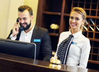 A male and female reception worker working together in a hotel