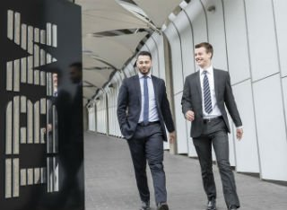 Two Surrey students walk outside the IBM sign during their work placement
