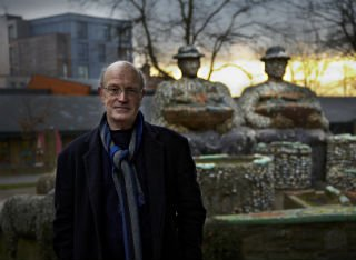 Iain Sinclair stood outside a statue and dark sky