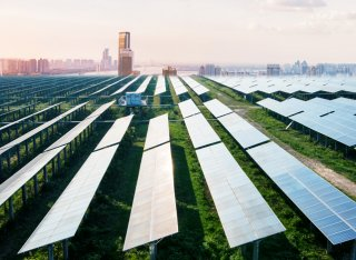 Field of solar panels with a city in the background