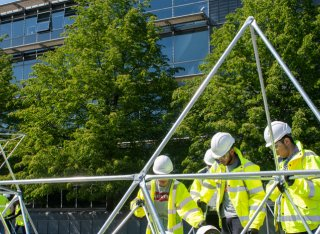 Civil engineering students at the University of Surrey outside of the Duke of Kent building building a construction