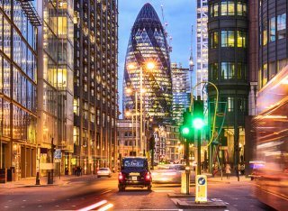 An evening photo of London with the gherkin building in the background and fast moving traffic