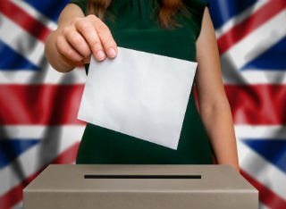 An anonymous woman posts her voting form into a UK ballot box