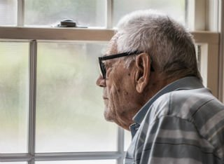 An elderly man looks out of a window