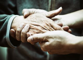 An elderly person's hand if being held by a younger person's hand